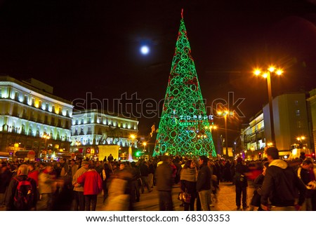 MADRID, SPAIN - DECEMBER 22: People have fun in Christmas time  the famous illuminated christmas tree at puerta del sol on December 22, 2010 in Madrid, Spain.
