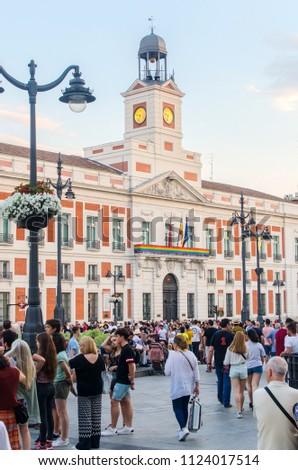 MADRID, SPAIN - JUNE 29, 2018: People in puerta del Sol in Madrid. Real casa de Correos is decorated with gay flag during gay pride week