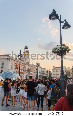 MADRID, SPAIN - JUNE 29, 2018: People in puerta del Sol in Madrid watching an street show. Real casa de Correos is decorated with gay flag during gay pride week