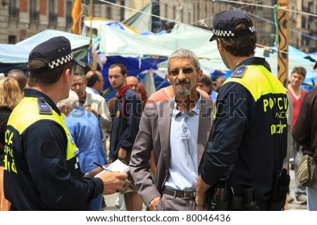 MADRID, SPAIN - JUNE 6: Police question a man on Puerta del Sol Square June 6, 2011 in Madrid. These protests are known as the Spanish Revolution days in Madrid.