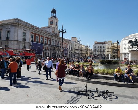 Madrid, Spain - March 2017: Puerta del Sol public square full of people, a bike in the floor and the House of the Post Office in a sunny cloudless day