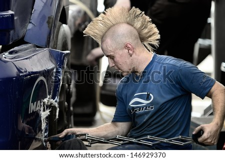 MADRID, SPAIN - OCT 10 : A mechanic repairing a MAN truck in the XXIV GP of Spain during the the 2011 FIA Truck Racing season, on Oct 10, 2011 in Madrid, Spain.