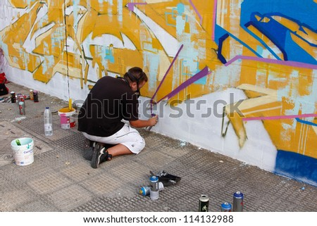 MADRID, SPAIN-SEPT. 18 : Unidentified man draws on the wall with a can of spray during first International Graffiti and Dance on September 18, 2012 in Madrid, Spain.