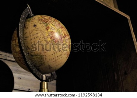 Madrid, Spain - September 22 2018: vintage globe illuminated partially by a soffused light #1192598134