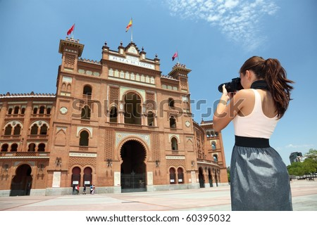 Madrid woman tourist photographer taking pictures of the bullfighting arena Plaza de Toros de Las Ventas in Madrid, Spain.