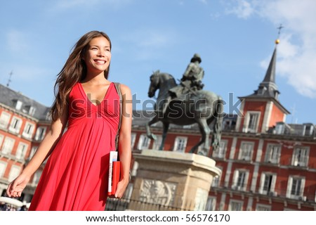 Madrid Woman tourist walking on Plaza Mayor Madrid Spain Beautiful woman in red dress Tourist attraction statue of Felipe III in the background