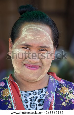 MAE HONG SONG, THAILAND - APRIL 13, 2015 : Portrait Myanmar woman with thanaka on her smile face is happiness. Thanaka is a yellowish-white cosmetic paste made from ground bark.
