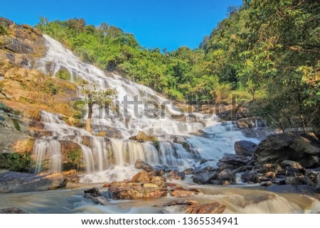 Mae Ya Waterfall, view of silky water flowing from high cliff around with arch rocks and green forest with blue sky background, Chom Thong District, Chiang Mai, Thailand. #1365534941