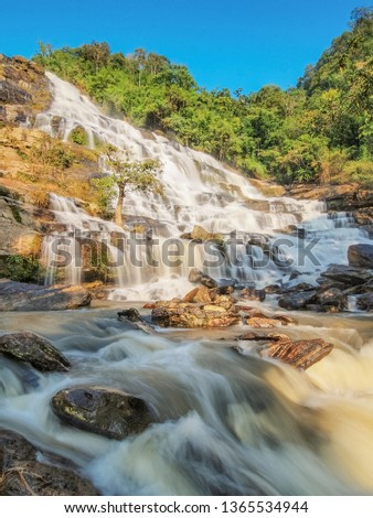 Mae Ya Waterfall, view of silky water flowing from high cliff around with arch rocks and green forest with blue sky background, Chom Thong District, Chiang Mai, Thailand. #1365534944