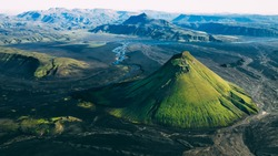 Maelifell green mountain in the lava black sand desert in Iceland, icelandic highlands, sunlight blue sky aerial drone capture of the landscape background on sunset sunrise yellow light