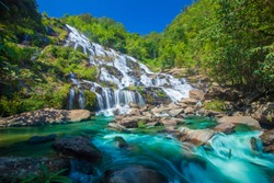 Maeya waterfalls cascade flowing in tropical forest and sun light at Doi Inthanon National park , a beautiful stream water famous rainforest , Chiang Mai province, Thailand.