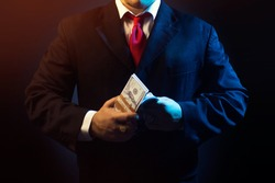 Mafia man in suit counting money on black background.