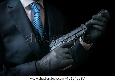 Stock Photo Mafia man or racketeer holds pistol with silincer in hands. Low key photo.