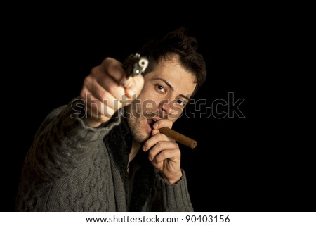 Mafia man smoking cigar with handgun, isolated over black background