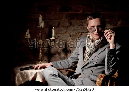 Mafioso. Man with a gun in a wicker chair on the background of an old brick wall