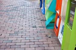 Magazine and newspaper racks after a rain on damp brick sidewalk