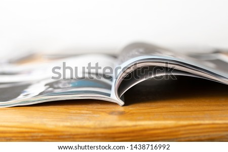 Magazine on wooden table. Beauty or fashion tips and trends. Open page with news article, column or celebrity interview. Media publication.