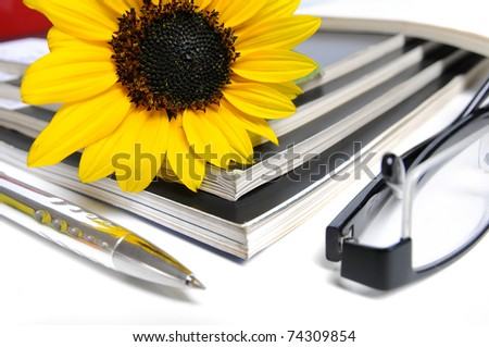 Magazines with sunflower - Glasses and ball point inf front over white background