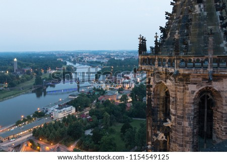 Magdeburg, Germany - June 9, 2018: View of one of the two towers of Magdeburg Cathedral with the river Elbe in the background and the famous lift bridge, Germany.