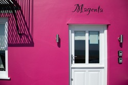 Magenta coloured old house. Front view. Colourful old UK house facade with text Magenta on it