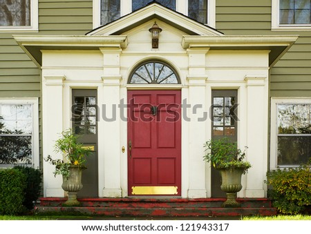 Magenta Home door bordered by two large potted plants