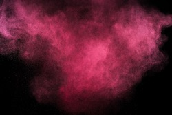 Magenta powder explosion on black background. Pink cloud. Red dust explode. Freeze motion paint Holi.