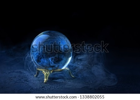 magic ball predictions. mysterious composition with glass magic ball and smoke on dark scene. Fortune teller, mind power, prediction concept. copy space