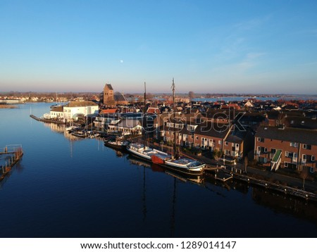Magic blue winterday in Grou Friesland the Netherlands. A view on a boat and the old church of Sint Piter. Every year this saint arrives in februari in this little watersports village. #1289014147