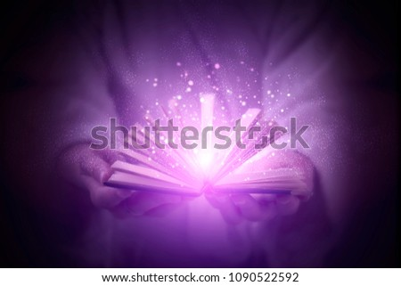 Magic book in the hands, magic, witchcraft, magic particles. The concept of magic on a dark background. Flash Light #1090522592