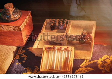Magic bottles and flasks with witching potion in the evening at sunset. Empty flask and ingredients for mystical spells are sold in retro store