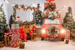 Magic card in red color. Decorated retro car with festive New Year lights, garlands, branches of Christmas trees, gift boxes in white-green wrapping paper, a wreath of pine needles. Copy space texture