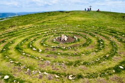 Magic Celtic spiral of life made of rocks in nature.