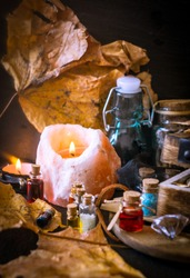 Magic concept. Potions in bottles, candles, box and orange leaves. Magical background