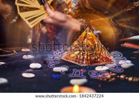 Magic divination and esotericism. Magic glass pyramid with a magical glow. In the background, a fortune teller holds a fan of Tarot cards. Close-up of hands