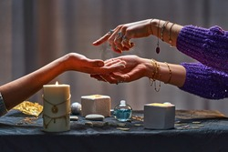 Magic gypsy woman reading palm lines around candles and other magical accessories. Witch during fortune telling palmistry, prediction the future life and divination ritual