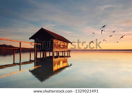 magic light at the beach - wooden jetty with boathouse at water #1329021491