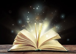 Magic light emanating from open old book on table