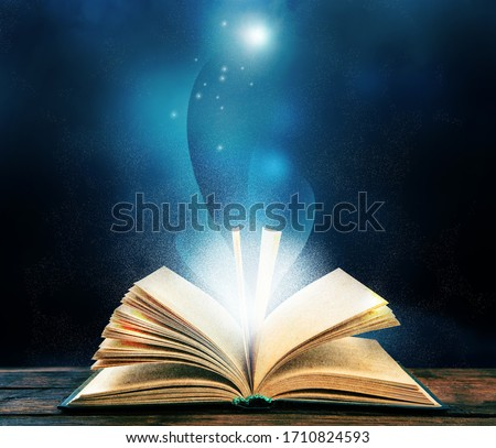 Magic light emanating from open old book on table Foto stock ©