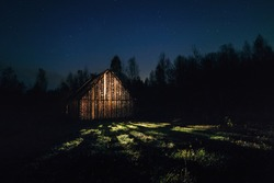 Magic light from an old barn at night. Starry sky above the house. Magical landscape. Wonders. Lamp illumination. Bright long rays shine from the house. Art park Nikola-Lenivets.