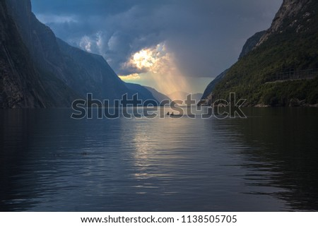 Magic lights above Lysefjord at Lysebotn, Norway. In the middle there is a Kanu with two people paddling into sunset.