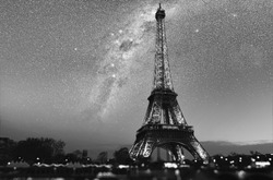 Magic night in Paris. Beautiful galaxy above an Eiffel tower silhouette. Black and white vintage style picture Elements of this image furnished by NASA.