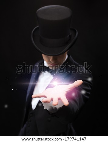magic, performance, circus, show and advertisement concept - magician holding something on palm of his hand #179741147