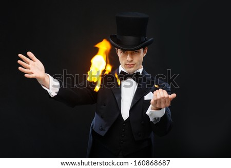 magic, performance, circus, show concept - magician in top hat showing trick with fire - stock photo
