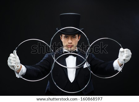 magic, performance, circus, show concept - magician in top hat showing trick with linking rings