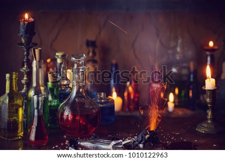Magic potion, ancient books and candles on dark background #1010122963
