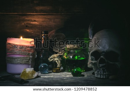 Magic potion and human skull on magic table background. Witchcraft concept. #1209478852