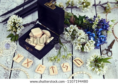 Magic runes in black box with spring wildflowers and decorations on table. Runes are ancient Scandinavian letters, no foreign words in the image