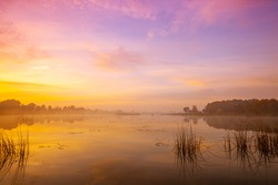 Magic sunrise over lake. Misty early morning, rural landscape, wilderness, mystical feeling. Serenity lake