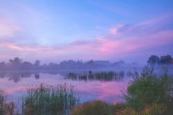 Magic sunrise over lake. Misty early morning, rural landscape, wilderness, mystical feeling. Serenity lake in magical light