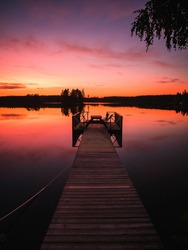 Magic sunset in summer night in Sweden. Dock or pontoon in lake with reflections of pink sky.